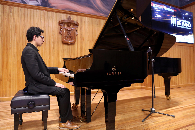 Un joven toca el piano marca Yamaha en el paraninfo