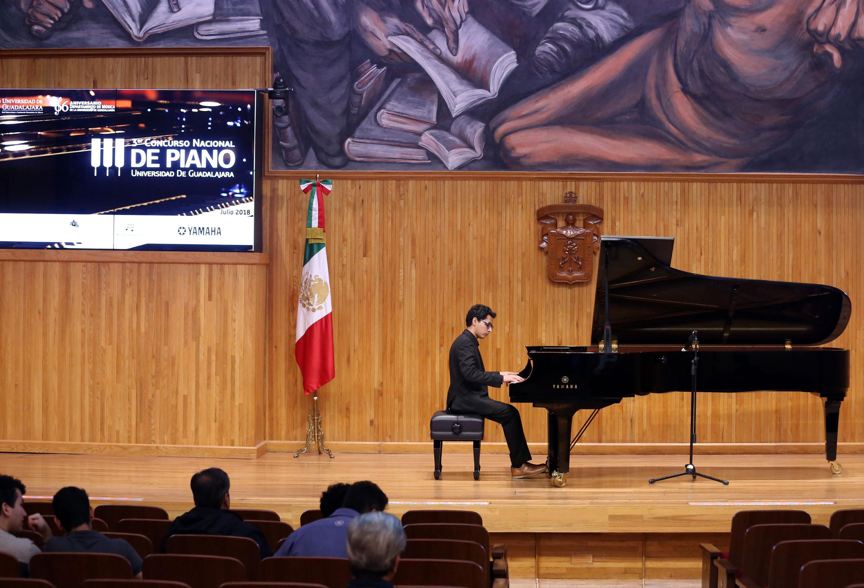 Un joven toca el piano en el paraninfo Enrique Díaz de León como parte del concurso