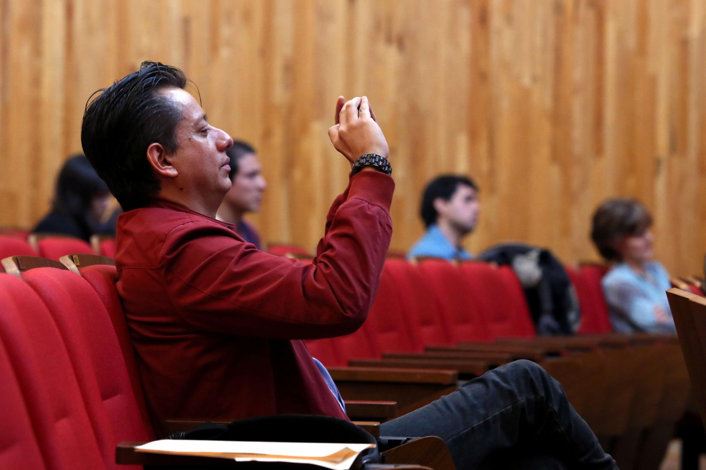 Un miembro de la audiencia toma video con su smartphone de uno de los participantes
