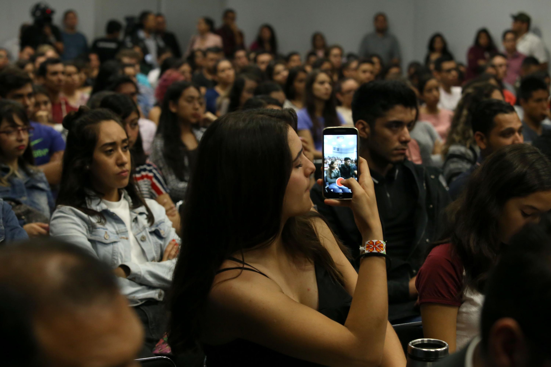 Joven muchacha distraida tomando fotos de la audiencia