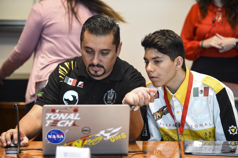 Integrantes de la Escudería TNT Racing by Tonaltech haciendo trabajos en computadora.