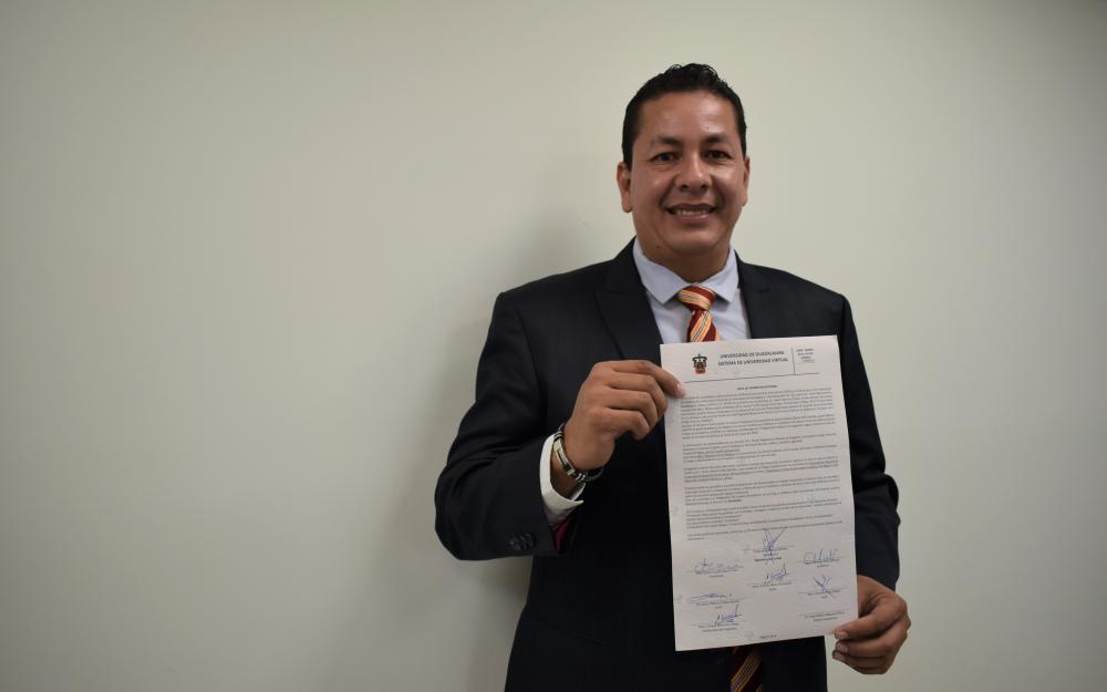 Egresado mostrando su carta de titulación como maestrante de la carrera en Gestión de Servicios Públicos en Ambientes Virtuales.