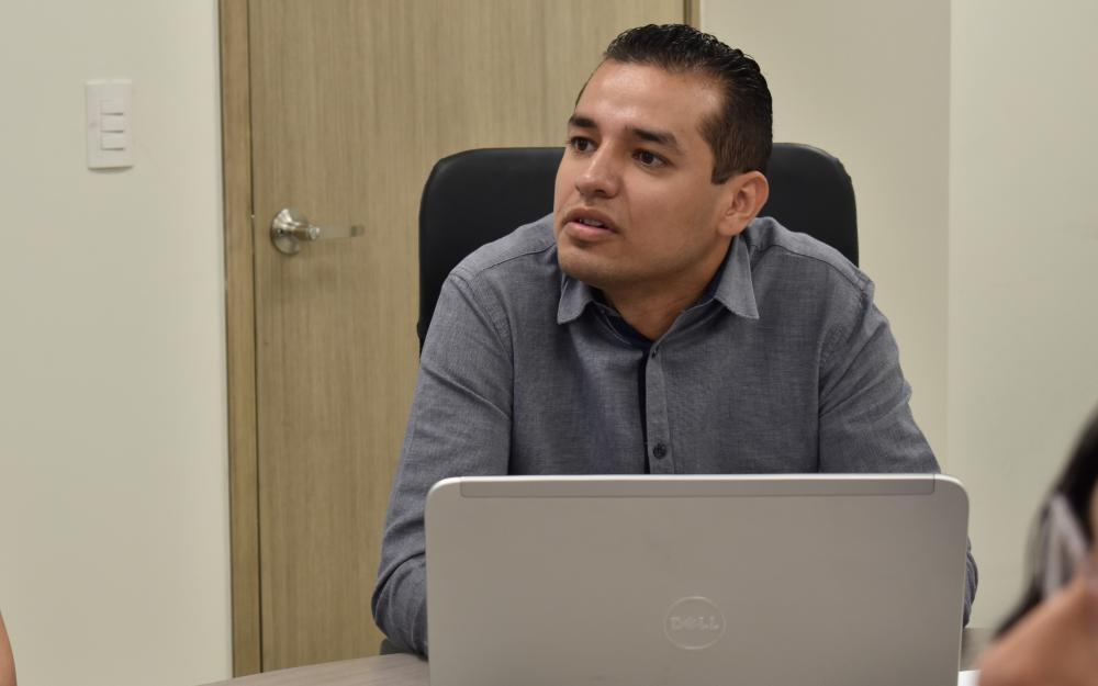Egresado  de la maestría en Gestión de Servicios Públicos en Ambientes Virtuales, de UDGVirtual, en frente de su laptop, haciendo uso de la palabra.
