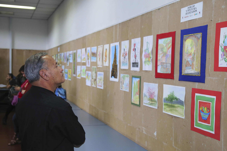 Un hombre mayor observa la exposicion de trabajos finales de estudiantes del SUAM UDG