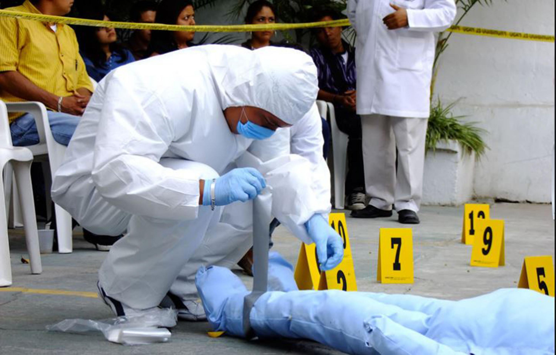 Un estudiante de ciencias forenses realizando una practica en presencia de publico
