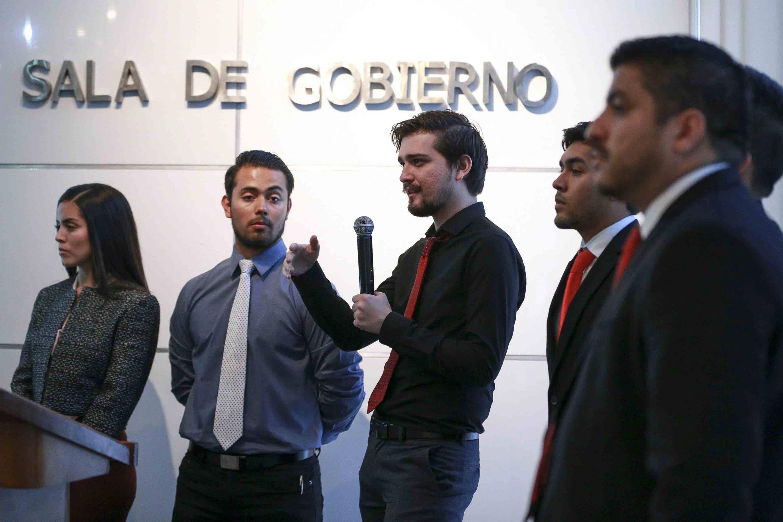 Estudiante concursante, en la sala de Gobierno dentro de las instalaciones del CUCEA, con micrófono en mano, haciendo uso de la palabra.