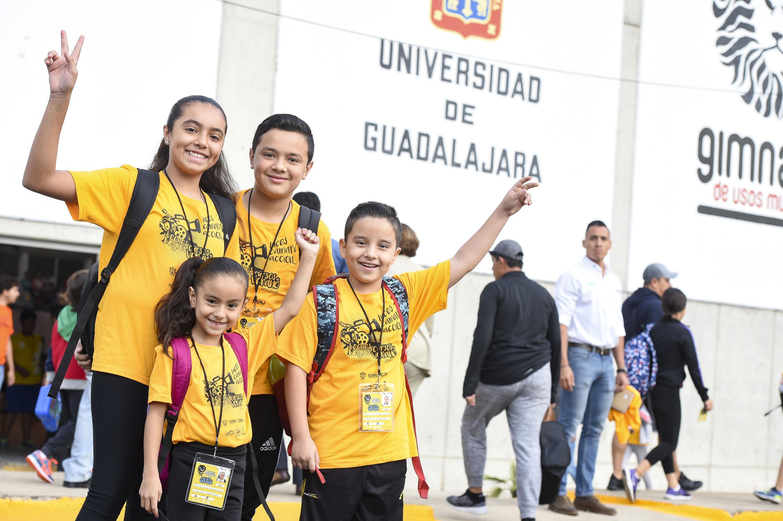 Cuatro niños sonriendo a la cámara.