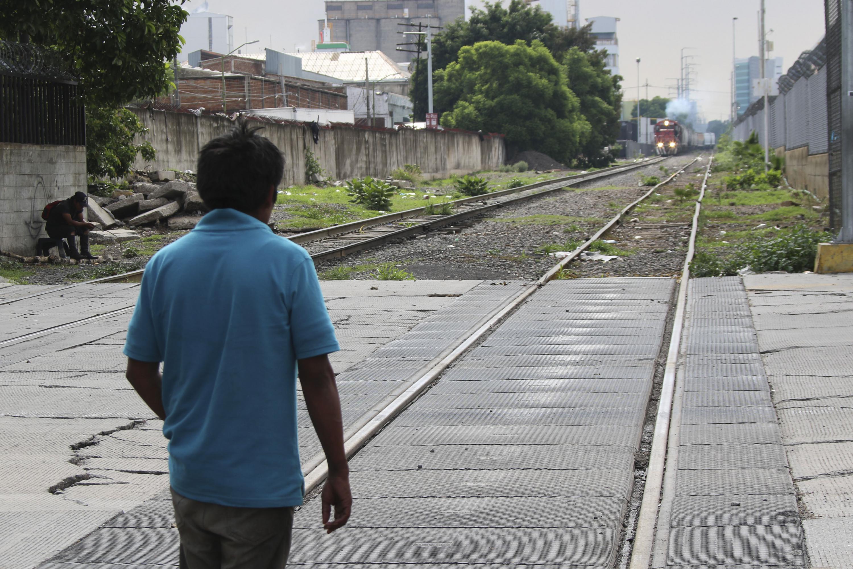 Un hombre camina sobre las vias del tren