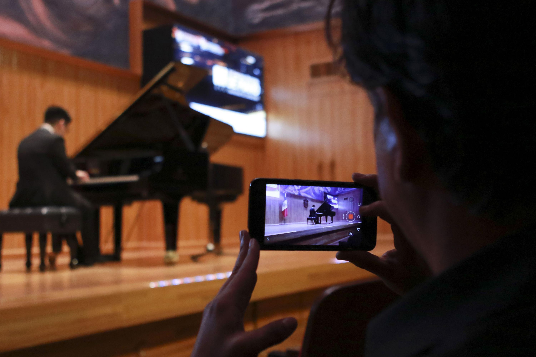 Un asistente graba con su teléfono inteligente a un pianista en plena presentación