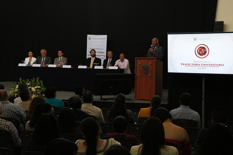 El rector de CUSUR habla desde el podium y lo escuchan los 6 miembros del presidium y el publico assitente