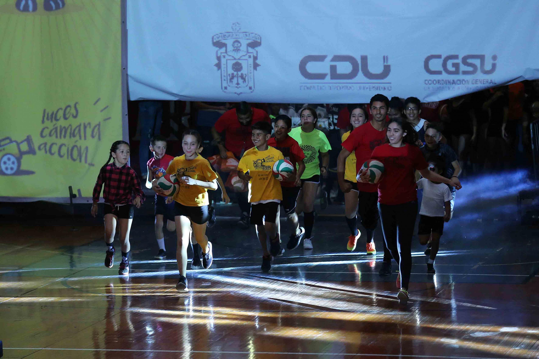 Niños y niñas participantes en el curso de verano del Complejo Deportivo Universitario (CDU) saliendo corriendo tras bambalinas, hacia el escenario principal.