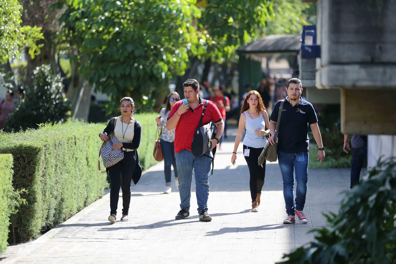 Estudiantes caminando por pasillos de centro universitario de la Universidad de Guadalajara