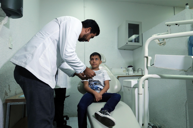 Un medico del CUCS inspecciona al niño en la clinica de protesis