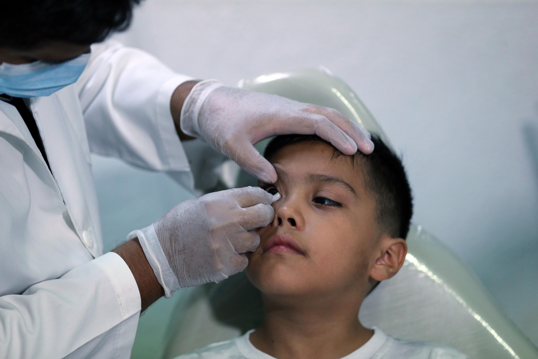 El niño pacientemente espera que el doctor termine el procedimiento
