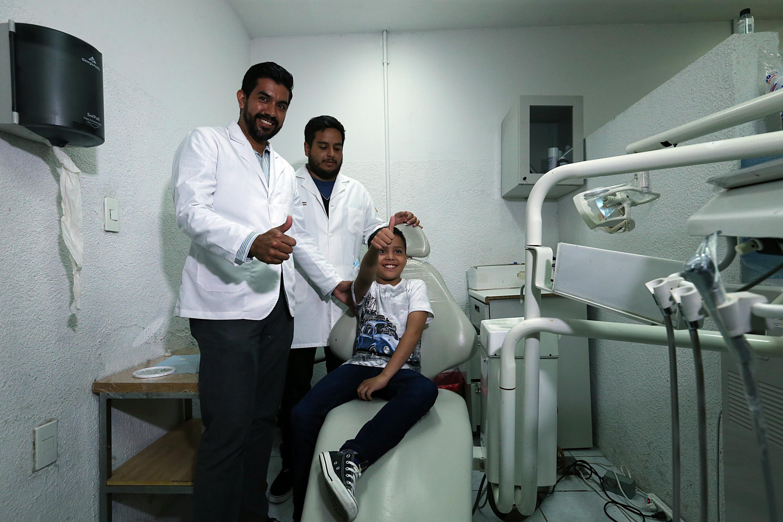 Dos medicos y el niño posan para la camara despues de la colocacion de la protesis ocular