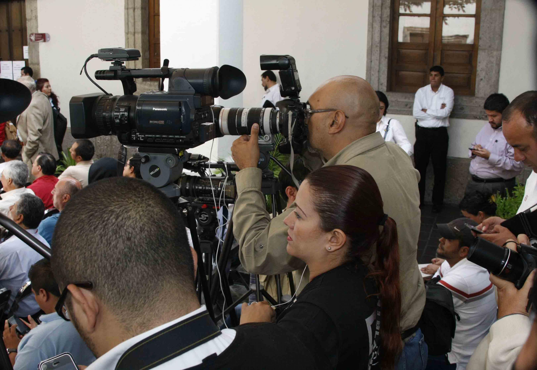 Periodistas y camarógrafos, cubriendo un evento.