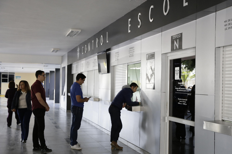 Aspirantes a licenciaturas de la UdeG, haciendo fila en una de las ventanillas de Control Escolar de la Universidad para realizar trámite de registro de ingreso..