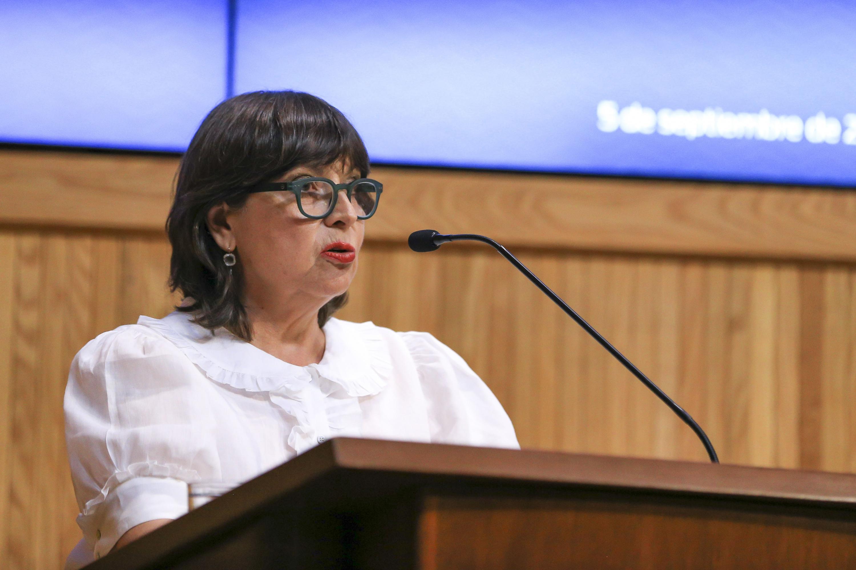 La academica hablando desde el podium a la audiencia