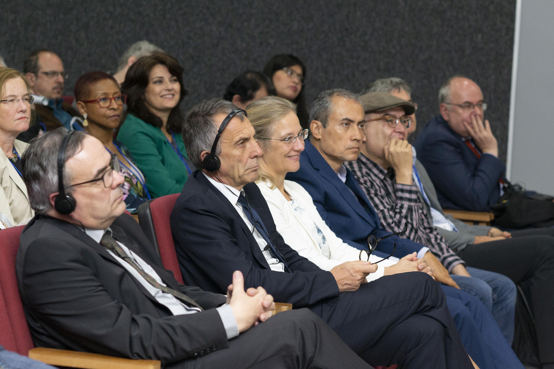 Los asistentes a la Conferencia inaugural escuchan al doctor Nestor en traduccion simultanea