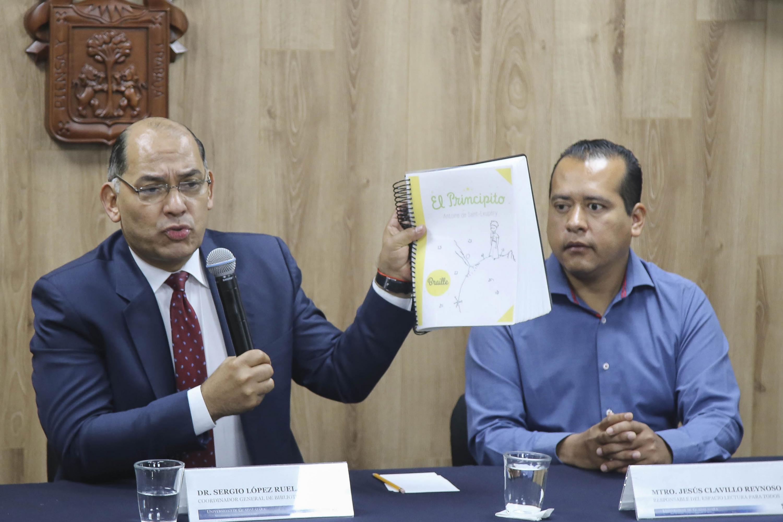 Coordinador General de Bibliotecas de la Universidad de Guadalajara (UdeG), doctor Sergio López Ruelas, sosteniendo el libro de el principito en braile, durante rueda de prensa