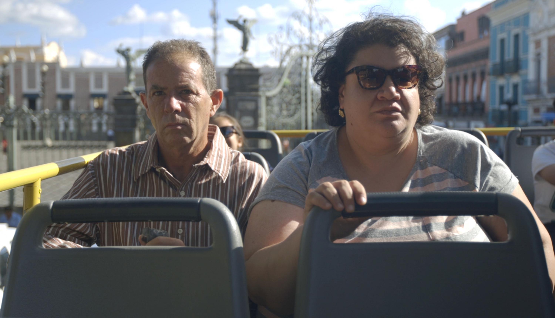 Un hombre adulto y una mujer mayor viajan en un transporte publico descubierto
