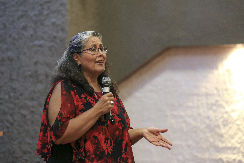 Doctora Martha Villaseñor Farías, académica del Centro Universitario de Ciencias de la Salud; con micrófono en mano haciendo uso de la palabra, durante su conferencia.