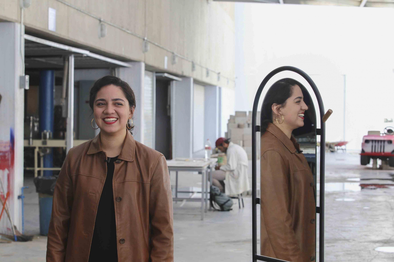 Margarita Torres Duarte, egresada de la licenciatura en Diseño Industrial del CUAAD; reflejandose en el espejo de la creación de su mueble.