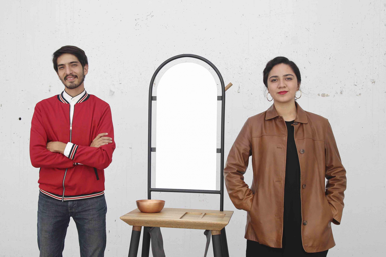 Irvyn García Rojo y Margarita Torres Duarte, egresados de la licenciatura en Diseño Industrial del CUAAD; posando a un lado de  su creación de mueble, ganador del concurso nacional Dimueble.