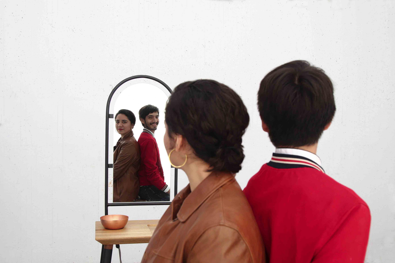 Credores del diseño puestos de entre espaldas, reflejándose en el espejo de su mueble ganador del concurso.
