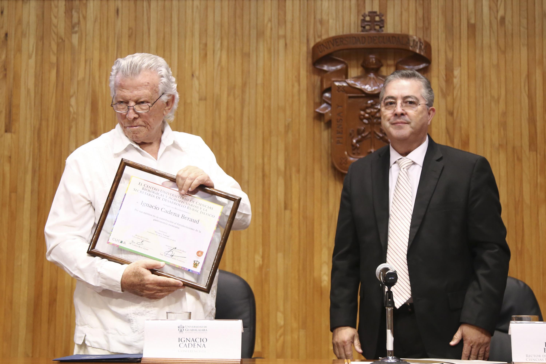 El chef Nacho Cadena sostiene el reconocimiento impreso que le fue entregado por el rector de CUCBA