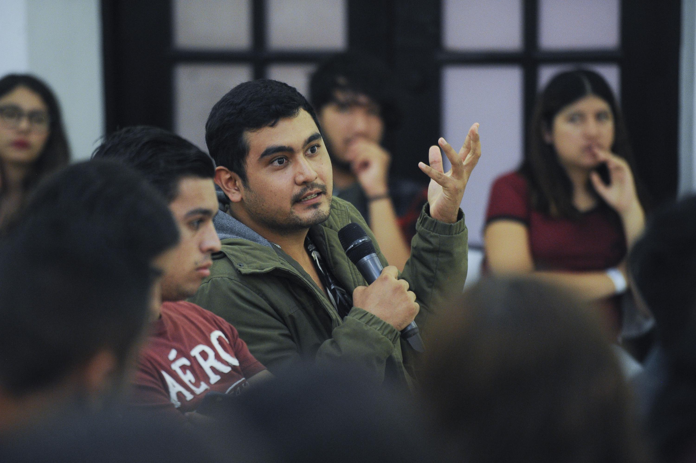 Un joven del publico realiza una pregunta al periodista