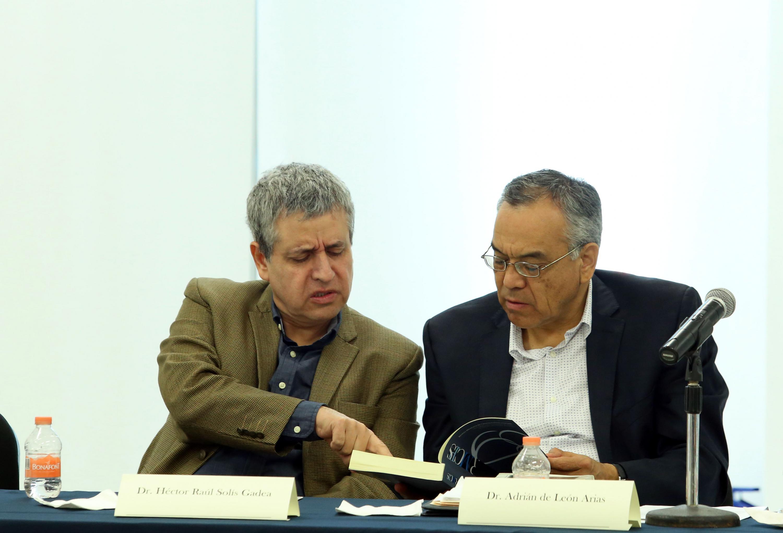 El  doctor Héctor Raúl Solís Gadea y el doctor Adrián de León Arias hablando entre ellos en el coloquio