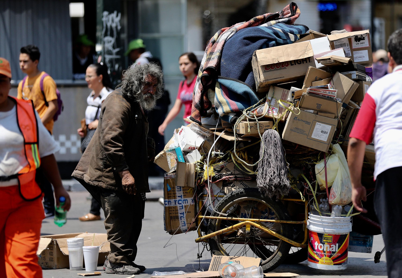 Un hombre adulto indigente que carga carton en un carrito
