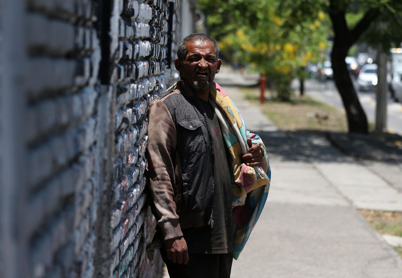 Un hombre indigente con una cobija infantil mirando hacia la camara