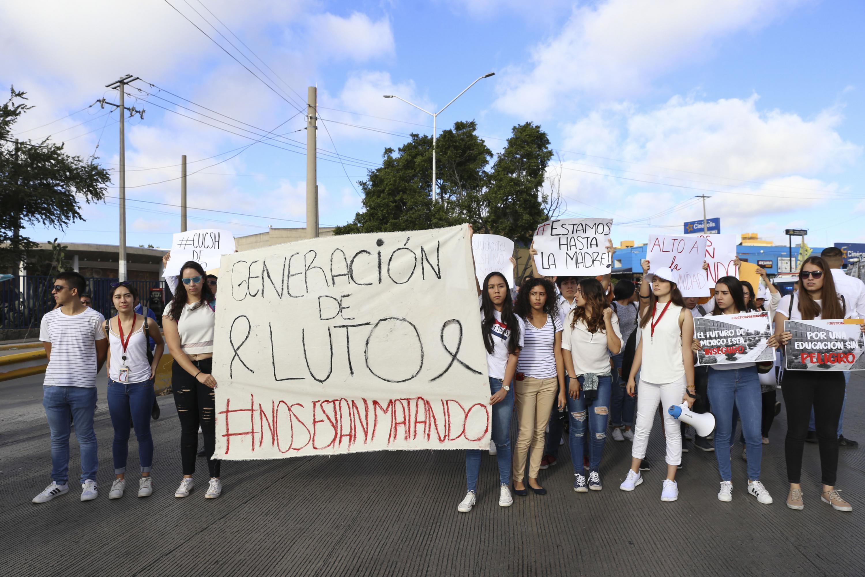 Unas estudiantes de CUCSH sostienen una gran manta que dice Generacion de Luto #NosEstanMatando