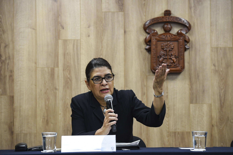 La doctora Celina Becerra hablando del evento frente a la sala de prensa de la UDG