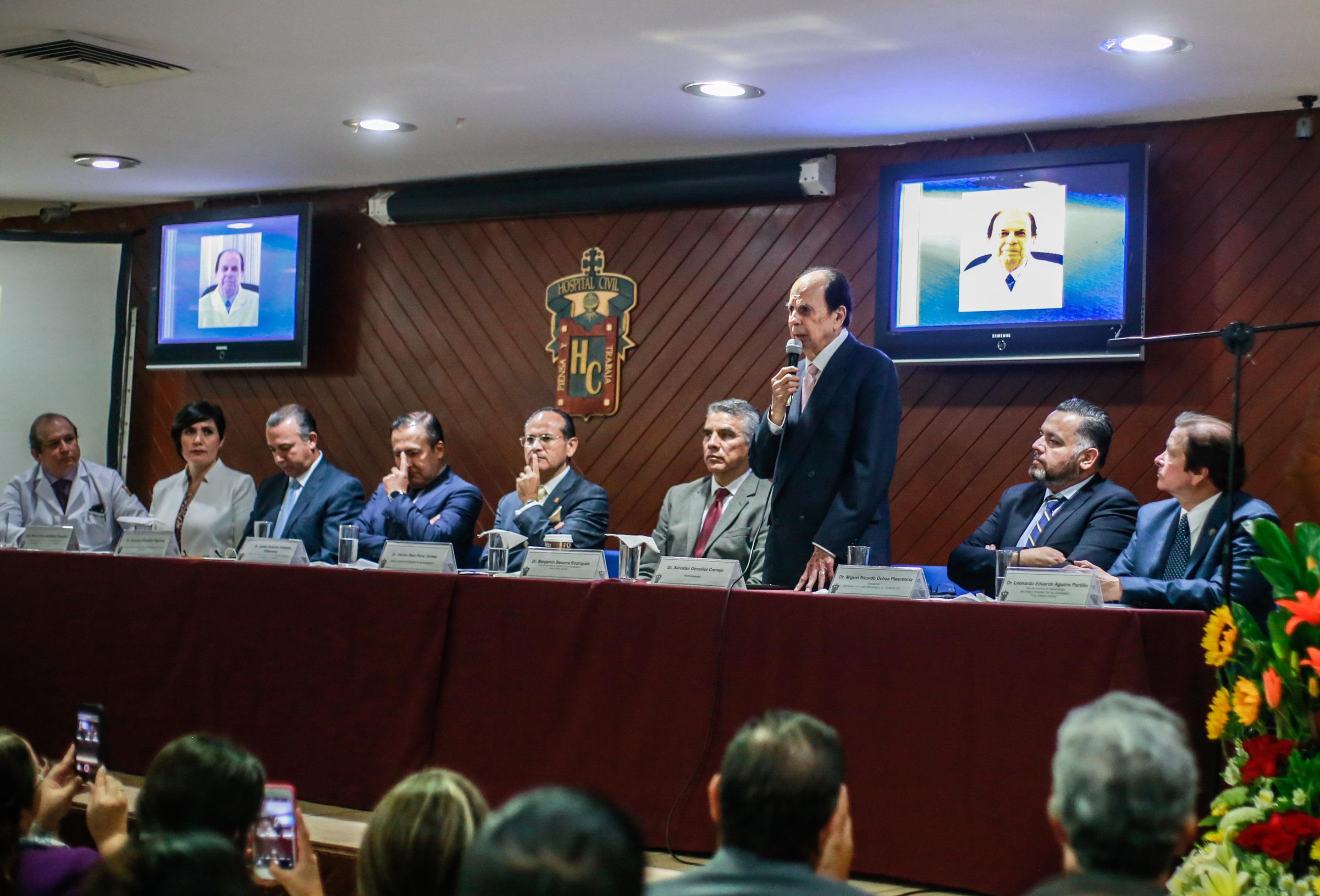 Dr. Salvador González Cornejo hablando de pie en el presidium a todos los asistentes