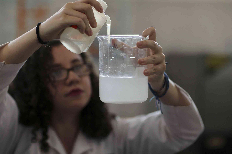 Una investigadora del CUCEI vierte un liquido en un vaso transparente