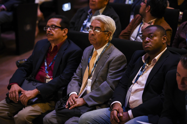 Tres hombres de diferentes nacionalidades escuchan la conferencia desde su lugar
