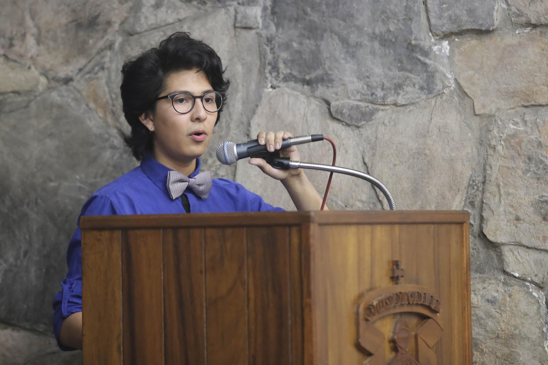 Una joven habla desde el podium. viste una camisa azul y un moño de corbata