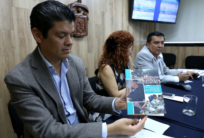 """Doctor Gabriel Flores Allende, mostrando un libro llamado """"Nuevas Realidades Juveniles"""""""