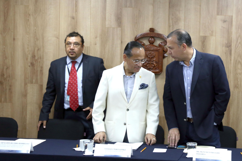 El director de ls Hospitales Civiles de Guadalajara y dos médicos tomando asiento antes de la rueda de prensa