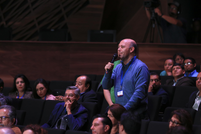 Un hombre del publico realiza una pregunta desde su lugar estando de pie