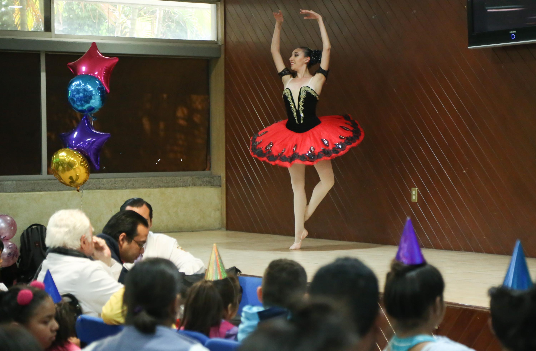 Pacientes pediátricos disfrutando del festival, mientras una bailarina de ballet, hace su actuación en l escenario del Auditorio de la Torre de Especialidades del Antiguo Hospital Civil.