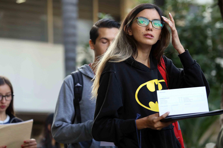 Una joven con playera de Batman espera su turno para ingresar