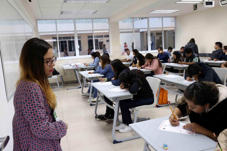 En el interior de un salon de clases los aspirantes realizan la prueba de aptitud academica