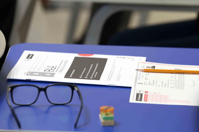 Un ejemplar de la Prueba de Aptitud Academica,junto a los lentes, lapiz e identificación de estudiante