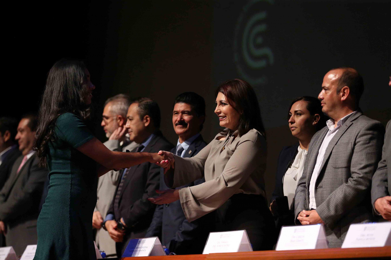 Vicerrectora Ejecutiva, doctora Carmen Rodríguez Armenta, haciendo de entrega una medalla a una alumna sobresaliente
