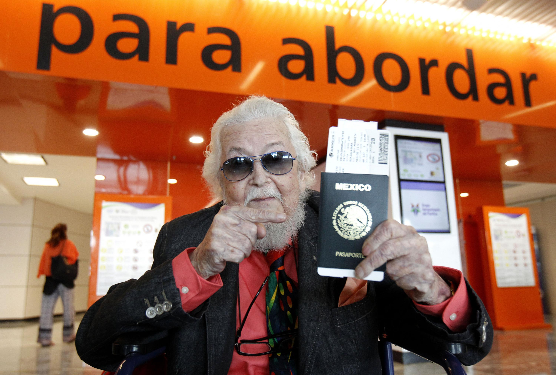 Fernando del Paso muestra su pasaporte mexicano durante una edicion de la FIL