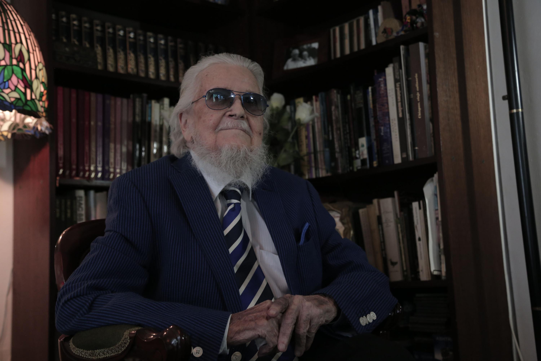 Fernando del Paso posando sonriente en su estudio personal
